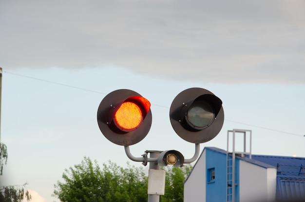 Сигнал перехода square grade с воротами на красный свет и перекладиной на железнодорожном переезде. светофор против снежной горы, пасмурное голубое небо.
