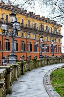 Площадь в центре итальянского города болонья. вид на аллею и фонари в стиле ретро