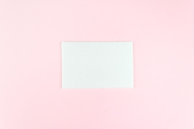 Square invitation card mockup on a soft pink background. flat lay, top view, copy space.