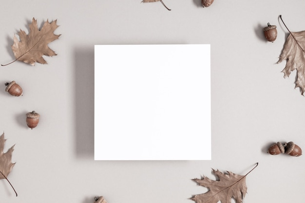 Square invitation card mockup with autumn leaves on gray background flat lay top view copy space