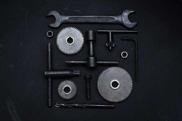 暗い背景にさまざまなツールの正方形のレイアウト。レンチツール、歯車、リングスパナ、モンキーレンチ。父の日。