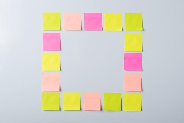 ホワイトボードにカラフルな付箋紙で作られた正方形