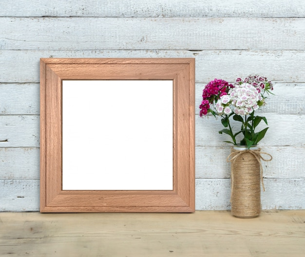 Square old wooden frame mockup near a bouquet of sweet-william stands on a wooden table on a painted white wooden background. rustic style, simple beauty. 3d render.