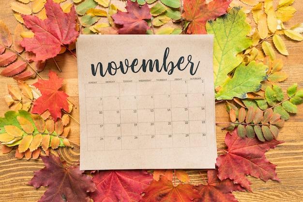 Квадратный лист бумаги ноябрьского календаря в окружении желтых и красных листьев на деревянном
