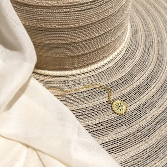 Square photo of beige summer hat and scarf with golden necklace on it