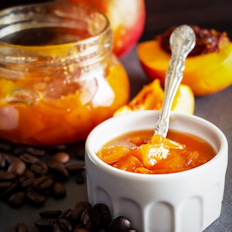 Square photo. nectarine marmelade in white ramekin and jar with coffee beans. dark space. selective focus. close up.