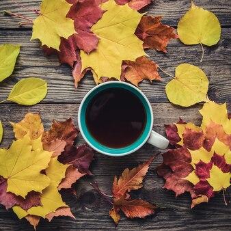 秋の黄色、オレンジ、紫の葉と木製の素朴な背景に紅茶のカップの正方形の画像