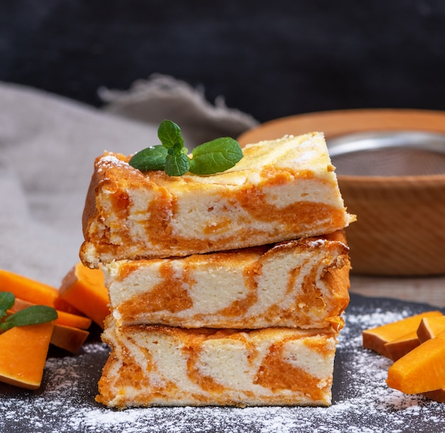 Square pieces of cheesecake with pumpkin