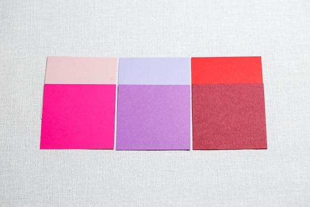 Квадратные кусочки разноцветной ткани, выложенные на сером фоне