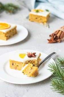 Square pieces of raw carrot cake with orange, nuts and cream cheese frosting. healthy food.