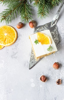 Square pieces of raw spiced carrot cake with orange, nuts and cream cheese frosting.