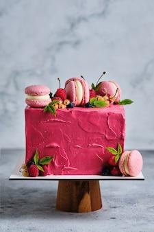 Квадратный розовый торт, украшенный макаронами и свежими ягодами. торт к празднику. десерт украшен свежей малиной, белой смородиной, вишней и черникой.