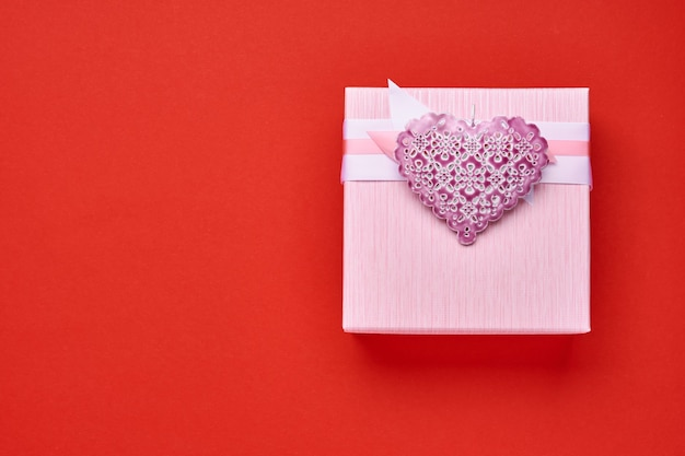 Square pink gift box with ribbon and heart on red background. valentines day concept postcard. top view.