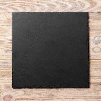 Square plate on table. black dish on wooden. copy space