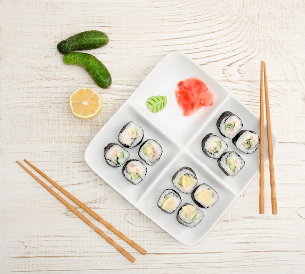 Square plate with rolls on a wooden table, ginger, cucumbers, lemon