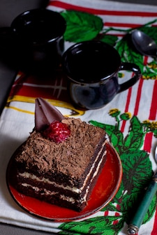 Square portioned cacao cake with white cream grated chocolate raspberry