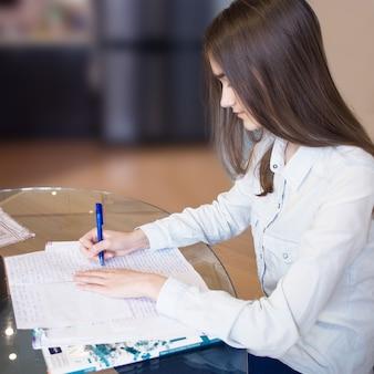 흐릿한 배경에 숙제를 하고 긴 금발 머리를 한 진지하고 아름다운 소녀의 정사각형 초상화. 10대 여학생이 테이블에 앉아 펜을 들고 공책에 글을 쓰고 있습니다. 측면보기