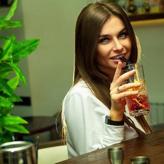 바 테이블에서 젊은 성적인 여자 음료 칵테일의 광장 초상화