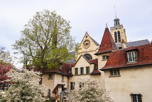 Площадь церкви сенлаурент в париже, франция с цветущими деревьями весной