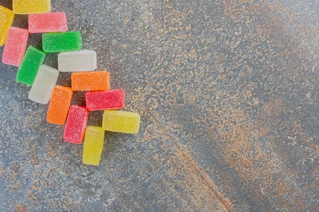Forma quadrata gelatina di caramelle sapore di frutta su uno sfondo scuro. foto di alta qualità