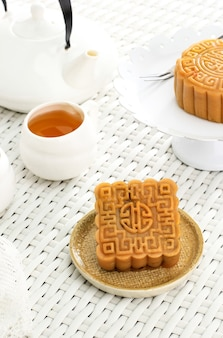 Square shape moon cake (mooncake) chinese dessert snack during lunar new year mid autumn festival. concept white asian bakery, served with tea
