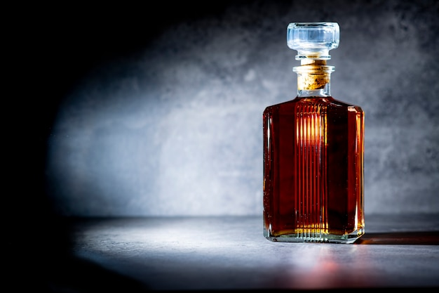 Square shaped whiskey bottle in rays of light on dark gray cement surface