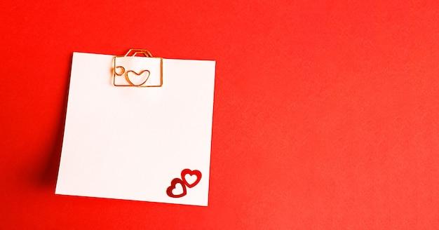 文字とハートの形をしたペーパークリップが付いたメモ用の正方形のシート