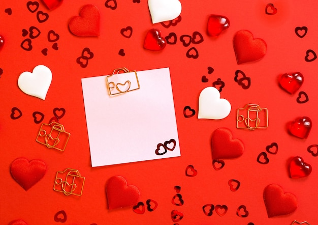 Square sheet for notes with a paper clip in shape of a letter and a heart.