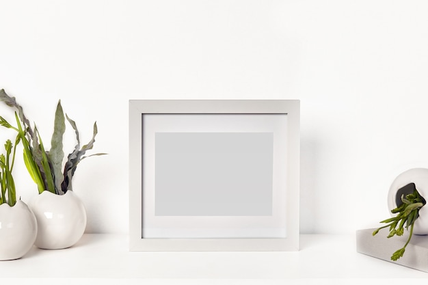 Square simple blank photo frame on tabletop surrounded by vases with green plants or flowers