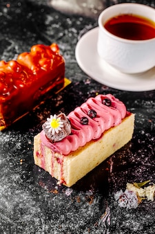A square slice of cake with pink cream and berries and another slice of red cake with a cup of tea.