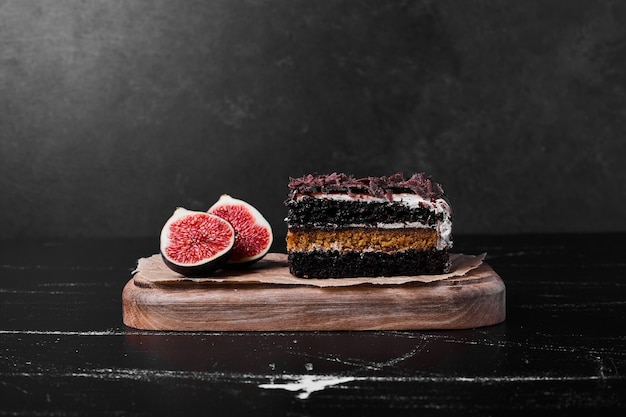 A square slice of chocolate cheesecake on black