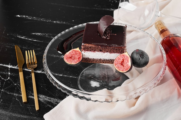 A square slice of chocolate cheesecake on a glass board.