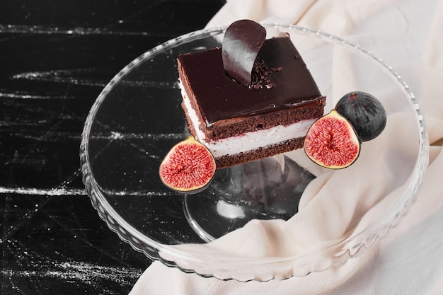 A square slice of chocolate cheesecake on a glass platter.