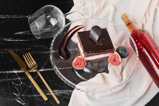 A square slice of chocolate cheesecake on a glass stand