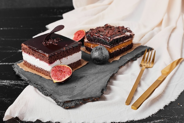 A square slice of chocolate cheesecake on a stone platter.