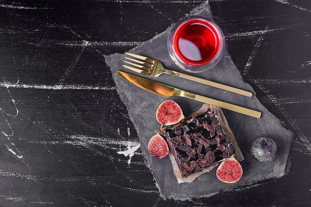 A square slice of chocolate cheesecake with red drink