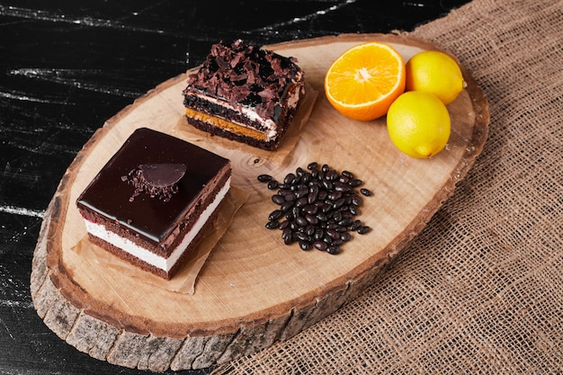 A square slice of chocolate cheesecake on a wooden board.