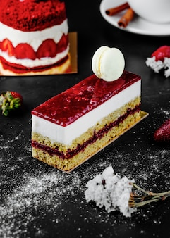 A square slice of strawberry cheesecake with white macaron on the top.