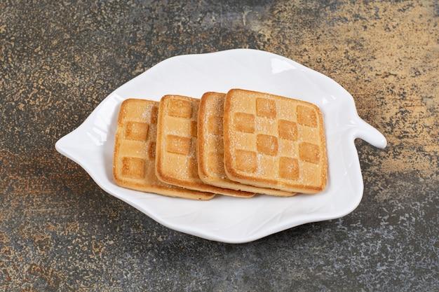 잎 모양의 접시에 사각 달콤한 크래커.