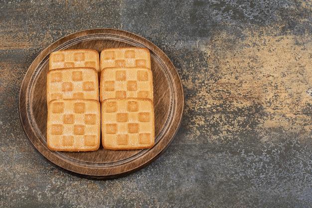 Cracker dolci quadrati sulla tavola di legno.