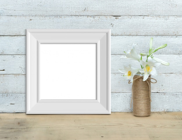 Square vintage white wooden frame mockup near a bouquet of lilies stands on a wooden table on a painted white wooden background. rustic style, simple beauty. 3d render.