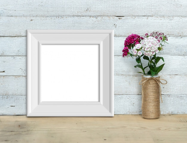 Square vintage white wooden frame mockup near a bouquet of sweet-william  stands on a wooden table on a painted white wooden background. rustic style, simple beauty. 3d render.