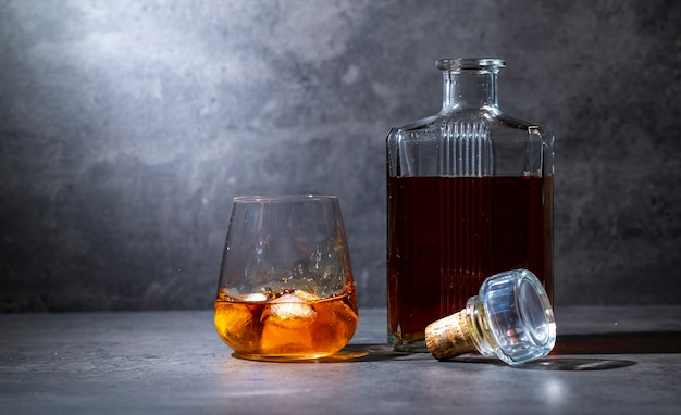 Square whiskey bottle and glass with ice on dark gray cement surface