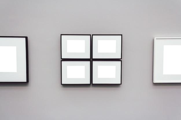 Cornici vuote bianche quadrate attaccate a una parete grigia
