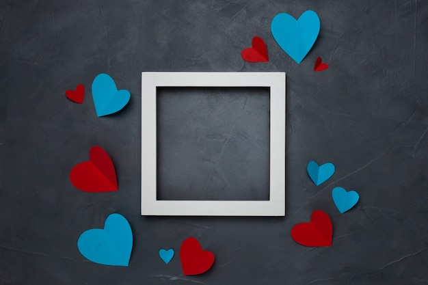 Square white empty frame with hearts on gray textured background with copyspace