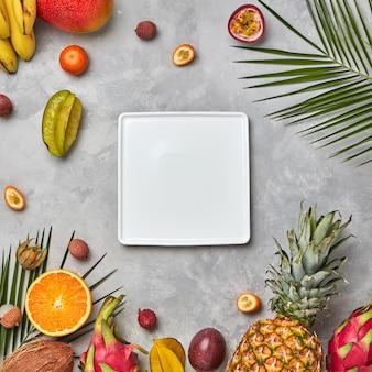 正方形の白い空のプレートナルミウムの葉とジューシーなトリオフルーツ、kumkva、サイ、パッションフルーツ、コピースペースのある灰色のコンクリートの背景にバナナ。食品組成。フラットレイ