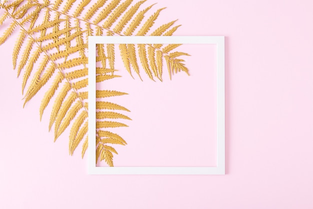 Square white frame and golden fern leaves on pastel pink background. minimalistic floral composition. flat lay.