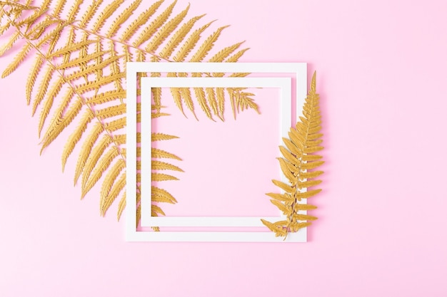 Square white frame and golden fern leaves on pastel pink background. minimalistic floral composition. flat lay
