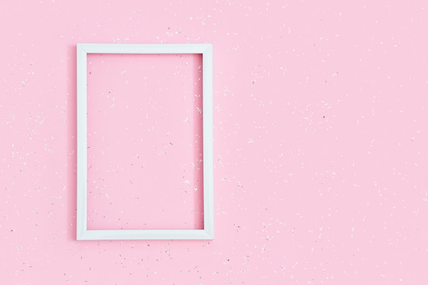 Square white frame  on pink paper background covered with sequins with copy space. birthday greeting card. invitation on festive.