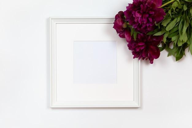 Квадратная белая рамка с букетом пионов на белом